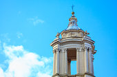 Top Part of the Cathedral . Church Baroque Architecture . Steeple with balcony . Religious Cross on the Top