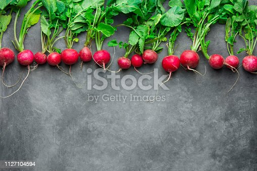 istock Top row of fresh raw organic red radishes with green leaves on dark concrete stone background. Vintage rustic style. Copy space for text. Vegan gardening balanced plant based diet 1127104594