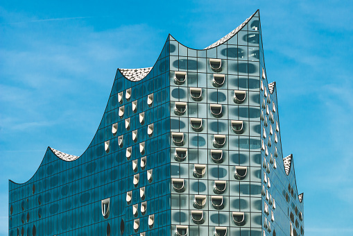 Top shape of Elbphilharmonie with white windows and some white clouds in sky, Hamburg, Germany
