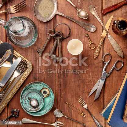 A top shot of many vintage objects, flea market stuff on a wooden table, a vintage background with a place for text