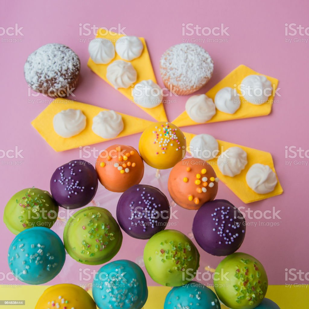 Top side view of cake pops on a colorful pink with yellow background royalty-free stock photo