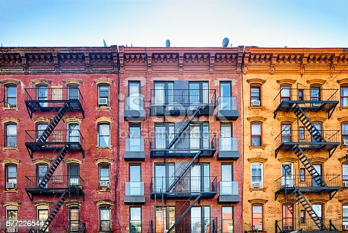 istock Top stories of colorful Williamsburg apartment buildings with steel fire escape stairways 877226544