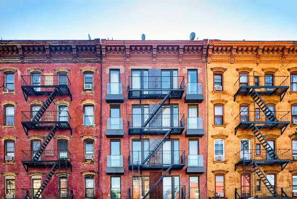 Top stories of colorful Williamsburg apartment buildings with steel fire escape stairways stock photo