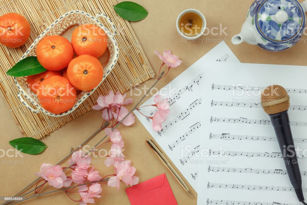 Top table view Chinese & Lunar new year with music sheet note paper concept background.space for creative design text or font.Essential item on the modern rustic brown wood at home office studio. stock photo