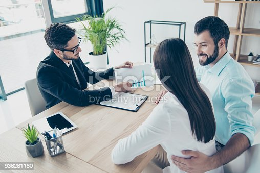 istock Top up high angle back view of joyful married couple, having consultation with a lawyer in his office, about a credit for buying purchase, all are dressed in formal outfits, smiling 936281160