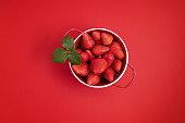 Top veiw of fresh and juicy strawberry on red background. Summertime, red fruits, vitamins, buy local, organic berries concept. Flat lay, copy space