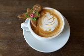 A cup of latte with a gingerbread cookie on elegant dark brown background. Closeup view. Cozy winter holidays composition.