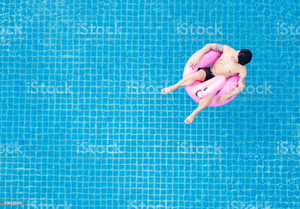 Top view, a man relaxing on pink flamingo swim pool float, on swimming pool in summer stock photo