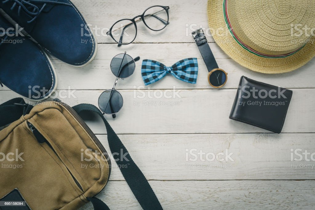 Top view accessoires to travel with man clothing concept. bow tie,wallet on wooden background.watch,sunglasses,bag,hat and shoes on wood table. stock photo