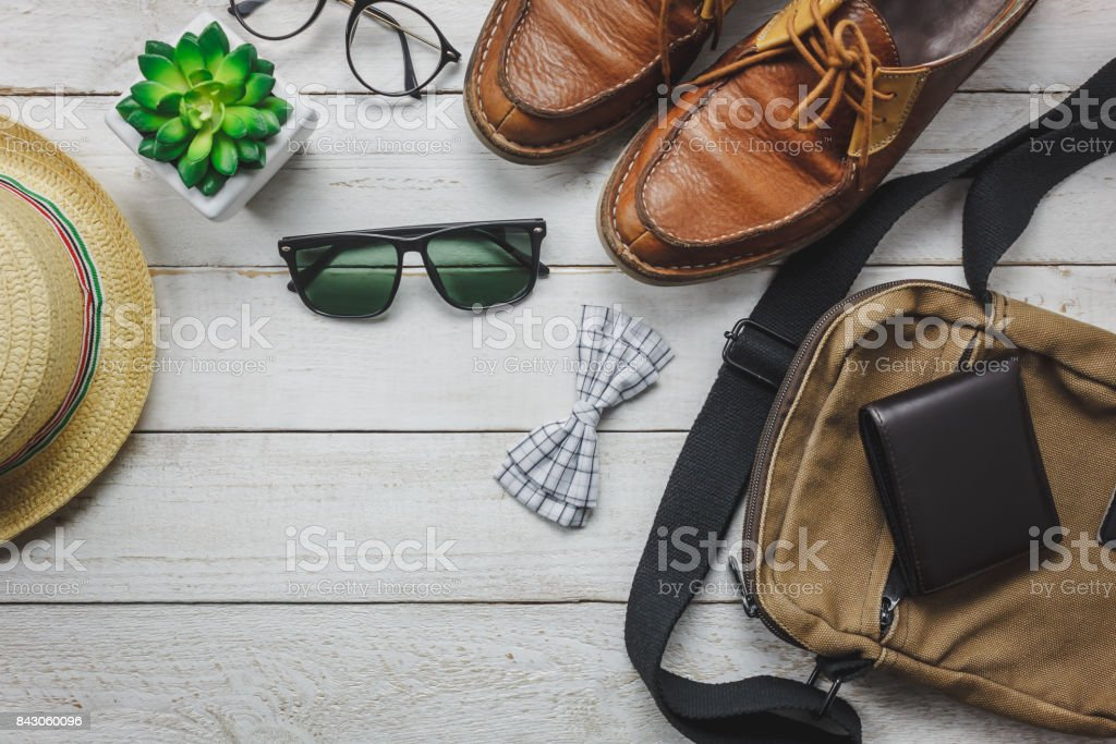 Top view accessoires to travel with man clothing concept. bow tie,wallet on wooden background.watch,sunglasses,bag,hat,belt and shoes on wood table. stock photo