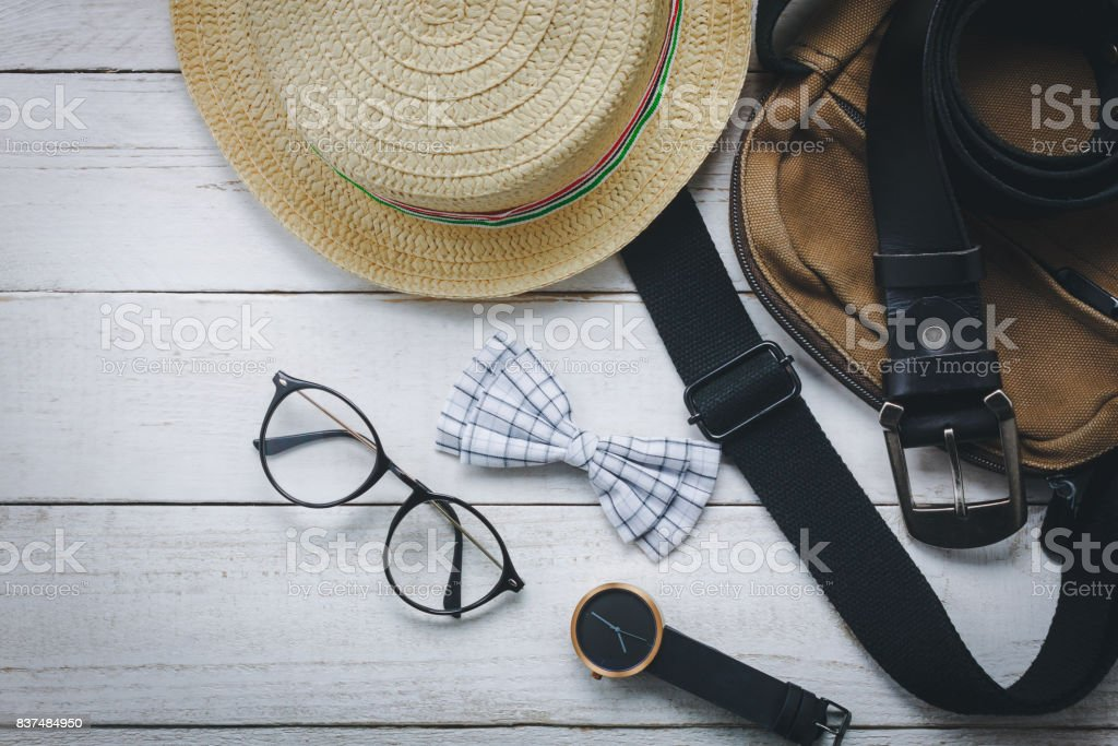 Top view accessoires to travel with man clothing concept. bow tie on wooden background.watch,eyeglasses,bag,hat on white wood table. stock photo