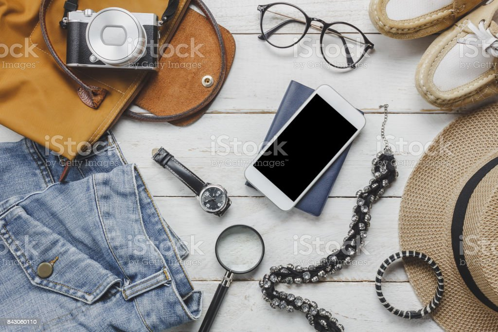 Top view accessoires to travel with women clothing concept. wallet on wooden background.watch,bag,hat,notebook,camera,necklace and shoe on white wood table. stock photo