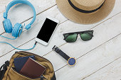 Top view accessories to travel concept.White mobile  phone listening music by headphone on wooden background.essential items for trip bag,passport,watch,sunglasses and hat on white wood table.