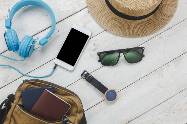 Top view accessories to travel concept.White mobile  phone listening music by headphone on wooden background.essential items for trip bag,passport,watch,sunglasses and hat on white wood table. stock photo