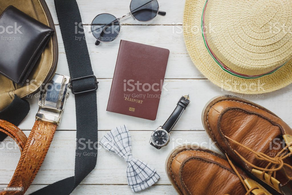 Top view accessories to travel with man clothing concept. bow tie,wallet on wooden background.watch,sunglasses,bag,hat and shoes on wood table. stock photo
