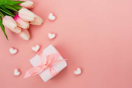 Top view aerial image of decoration Happy mother's day holiday background concept.Flat lay white present box with flower on modern beautiful  pink paper at home office desk.Free space for design.