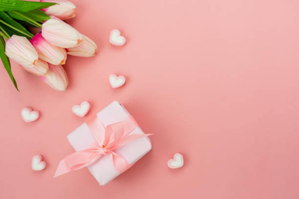 Top view aerial image of decoration Happy mother's day holiday background concept.Flat lay white present box with flower on modern beautiful  pink paper at home office desk.Free space for design. stock photo