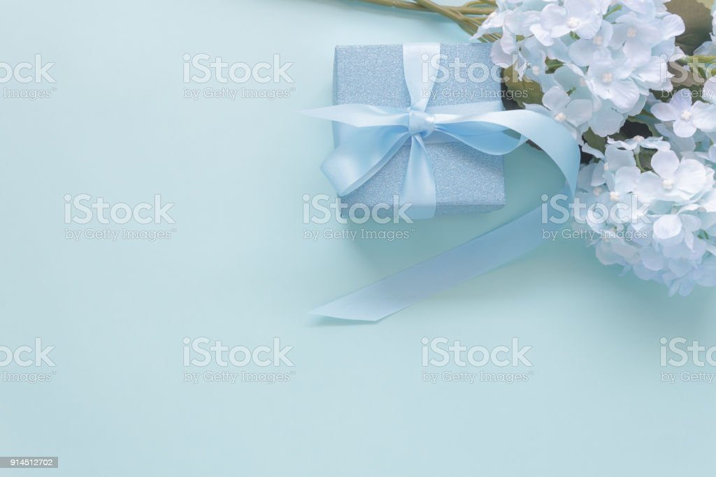 Top view aerial image of decoration Happy mother's day holiday background concept.Flat lay gift box with blue flower on modern beautiful  blue paper at home office desk.Free space for design. stock photo