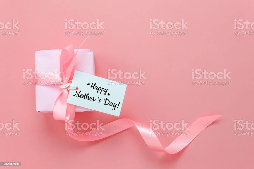Top view aerial image of decoration Happy mother's day holiday background concept.Flat lay mom white card with gift box on modern beautiful  pink paper at home office desk.Free space for design. stock photo