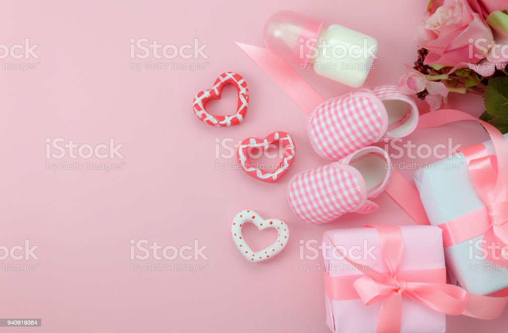 Top view aerial image of decoration Happy mother's day holiday background concept.Flat lay sign of season the pink rose with kid shoe and child toys  on pink paper at home office desk. stock photo