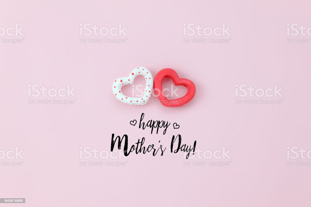 Top view aerial image of decoration Happy mother's day holiday background concept.Flat lay sign of season couple heart shape on pink paper at home office desk with creative design text for seasonal. stock photo