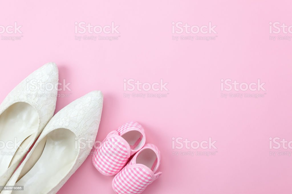 Top view aerial image of decoration Happy mother's day holiday background concept.Flat lay sign of season the pink rose with clothing woman & kid and child toys  on pink paper at home office desk. stock photo