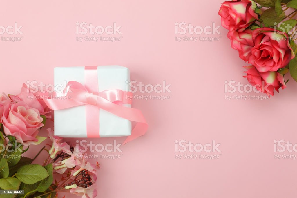 Top view aerial image of decoration Happy mother's day holiday background concept.Flat lay white present box with blue rose on modern beautiful  pink paper at home office desk.Free space for design. stock photo