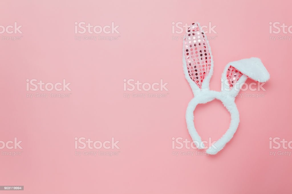 Top view aerial image of decoration & symbol Happy Easter holiday background concept.Flat lay accessory costume bunny ear on modern beautiful pink paper at home office desk.Free space for design. stock photo
