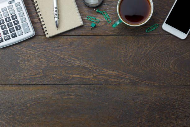 Top view aerial image shot of arrangement accessory business background concept.Flat lay black coffee & essential items pen and notebook with mobile phone on modern wooden table at home office desk. stock photo