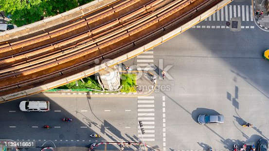 820883024istockphoto Top view aerial of a driving car on asphalt track and pedestrian crosswalk in traffic road with light and shadow silhouette with rail sky train. 1139416651