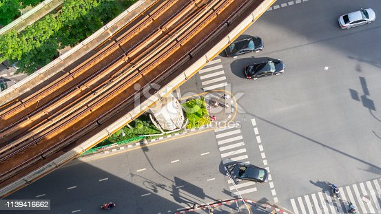 820883024istockphoto Top view aerial of a driving car on asphalt track and pedestrian crosswalk in traffic road with light and shadow silhouette with rail sky train. 1139416662