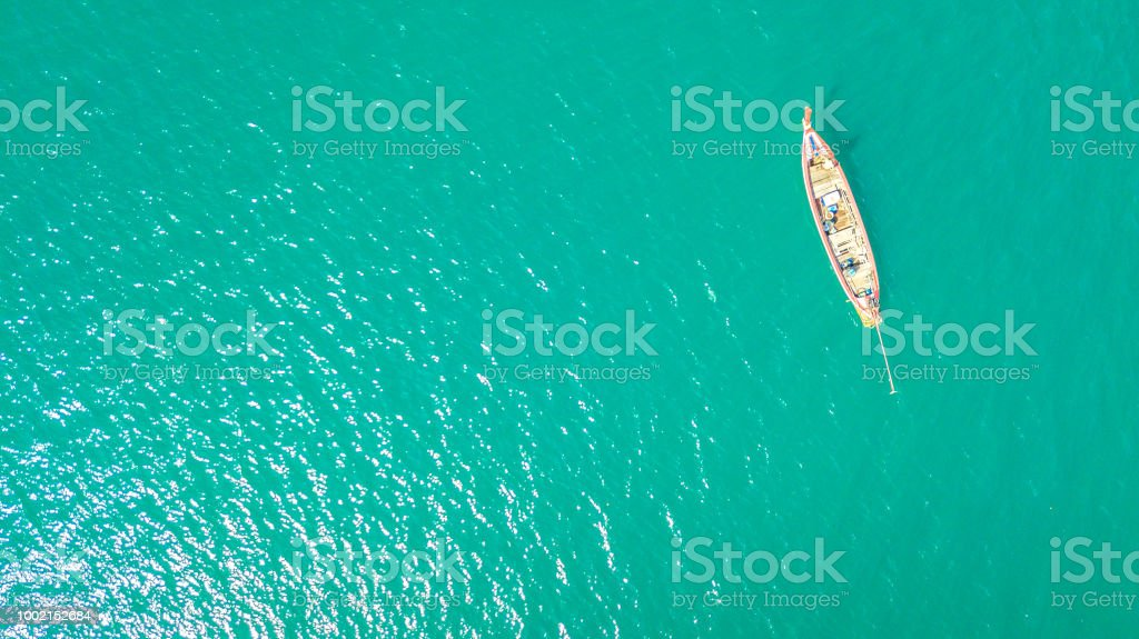 Top view Aerial view High angle view Small boat in the blue sea...
