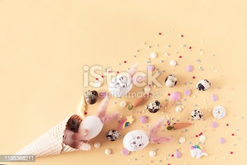 Top view and flat lay of conceptual arrangement decoration for Happy Easter holiday on yellow background. Colorful pastel eggs and topping spill out of the waffle horn with copy space.
