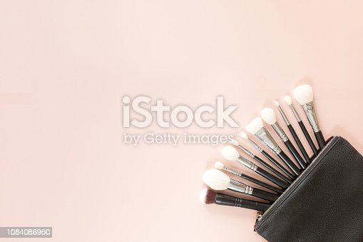 Top view and flat lay of set of makeup brushes in cosmetic bag on pink background, copy space. Beauty concept