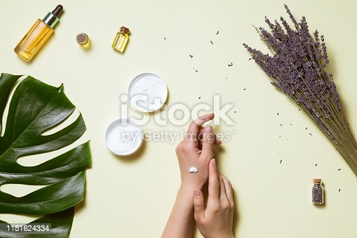 istock Top view and flat lay of woman holding cream on hands over white table with cosmetic products - avocado oil, cream and bamboo 1151624334