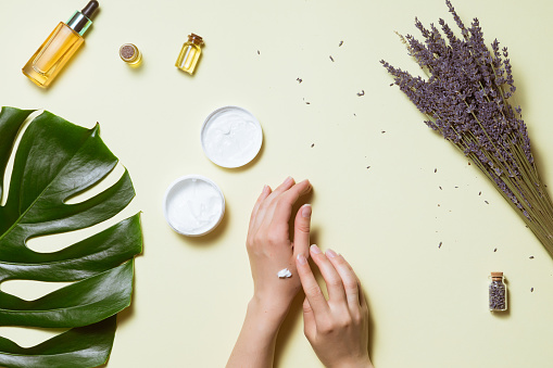 istock Top view and flat lay of woman holding cream on hands over white table with cosmetic products - avocado oil, cream and bamboo 1151624350