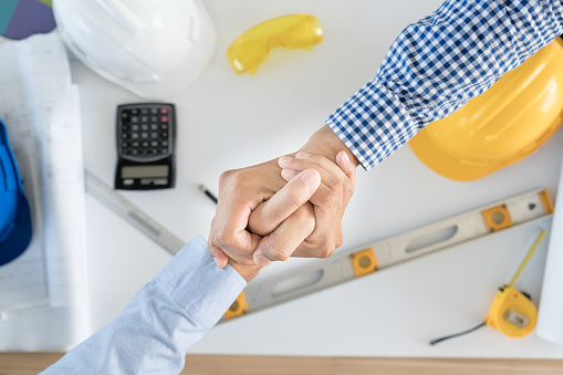 912867216 istock photo Top view Architect and engineer shaking hands, finishing up a meeting on building project and tools. Shaking hands agreement concept. 835926542