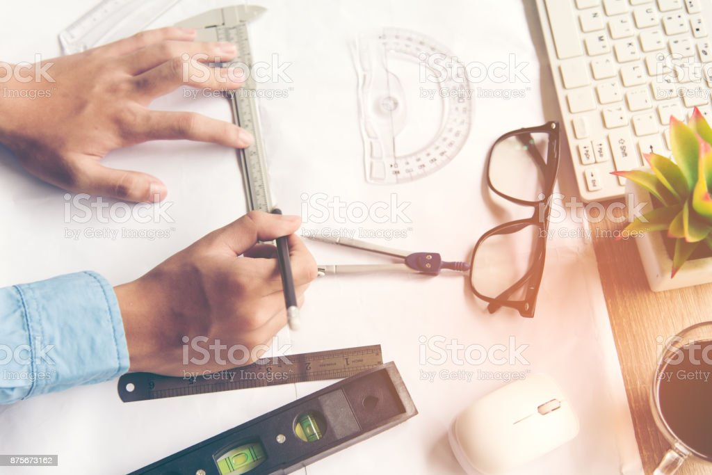 Top View Architect working on blueprint. Architects workplace.  Engineer tools and safety control,  blueprints, ruler, orange helmet,radio,laptop and divider compass. Construction Concept. select focus stock photo