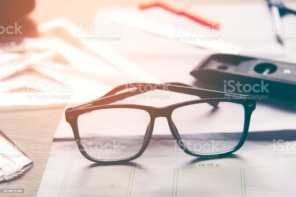 Top View Architect working on blueprint with back glasses. Architects workplace. Construction Concept. stock photo