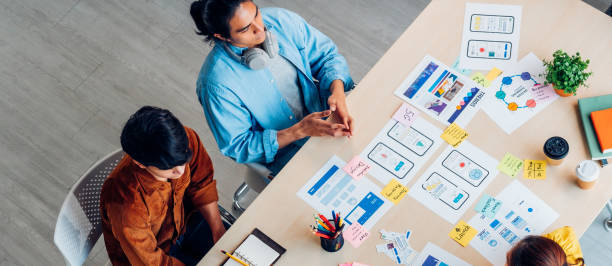 Top view asian ux developer and ui designer brainstorming about mobile app interface wireframe design on table with customer breif and color code at modern office.Creative digital development agency stock photo