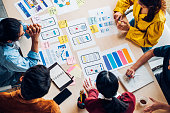 istock top view asian ux developer and ui designer brainstorming about mobile app interface wireframe design on table with customer brief and color code at modern office.Creative digital development agency 1218511457