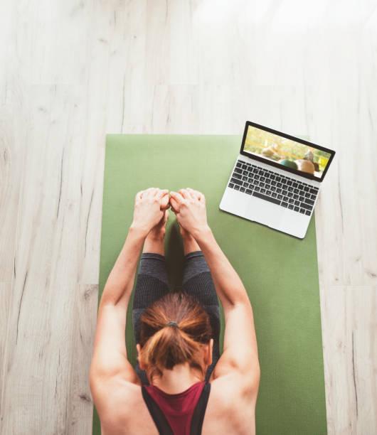 Vista superior en forma deportiva mujer sana sentada en la estera en Paschimottanasana pose, haciendo ejercicios de respiración, viendo clases de yoga en línea en la computadora portátil. Personas sanas y concepto de automotivación. - foto de stock