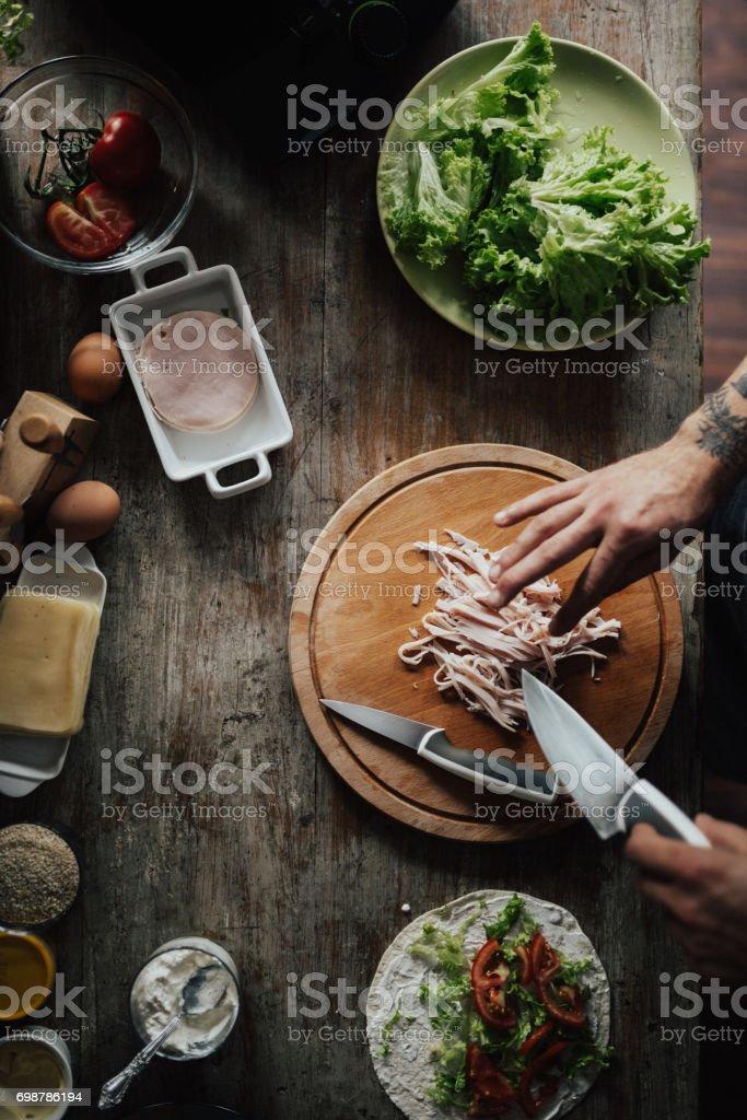 Draufsicht auf jemandes Hände schneiden Schinken in kleine Stücke – Foto