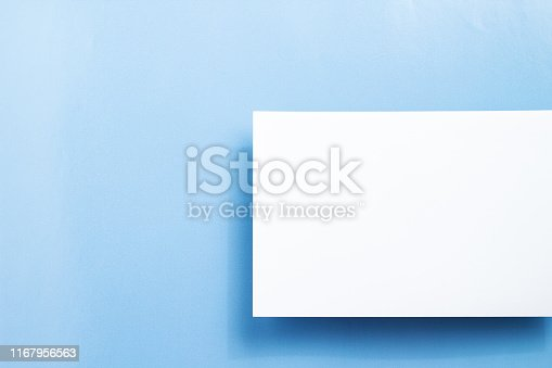istock Top view blank paper, white empty business card or flyer on blue background. Blank signboard with copy space area for text or slogan 1167956563