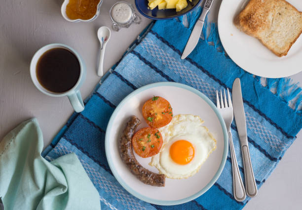 Top view breakfast background with sausage, fried egg, tomato, coffee, marmalade and toast stock photo