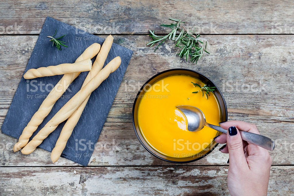 Top view - carrot soup and pumpkin in black bowl stock photo