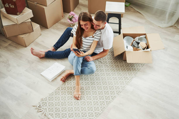 Top view. Cheerful young couple in their new apartment. Conception of moving stock photo