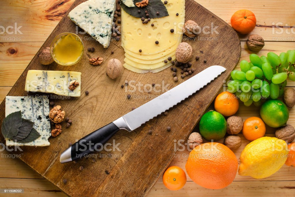 Top view cheese plate Assortment of various types of cheese on dark wooden cutting board stock photo
