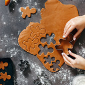 Top view christmas food concept. Woman is cooking gingerbread man cookies in Christmas on dark background, flat lay. Xmas dessert