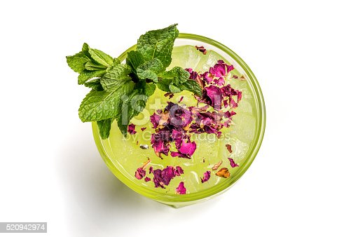 superior view of a green cocktail with mint and flower decored